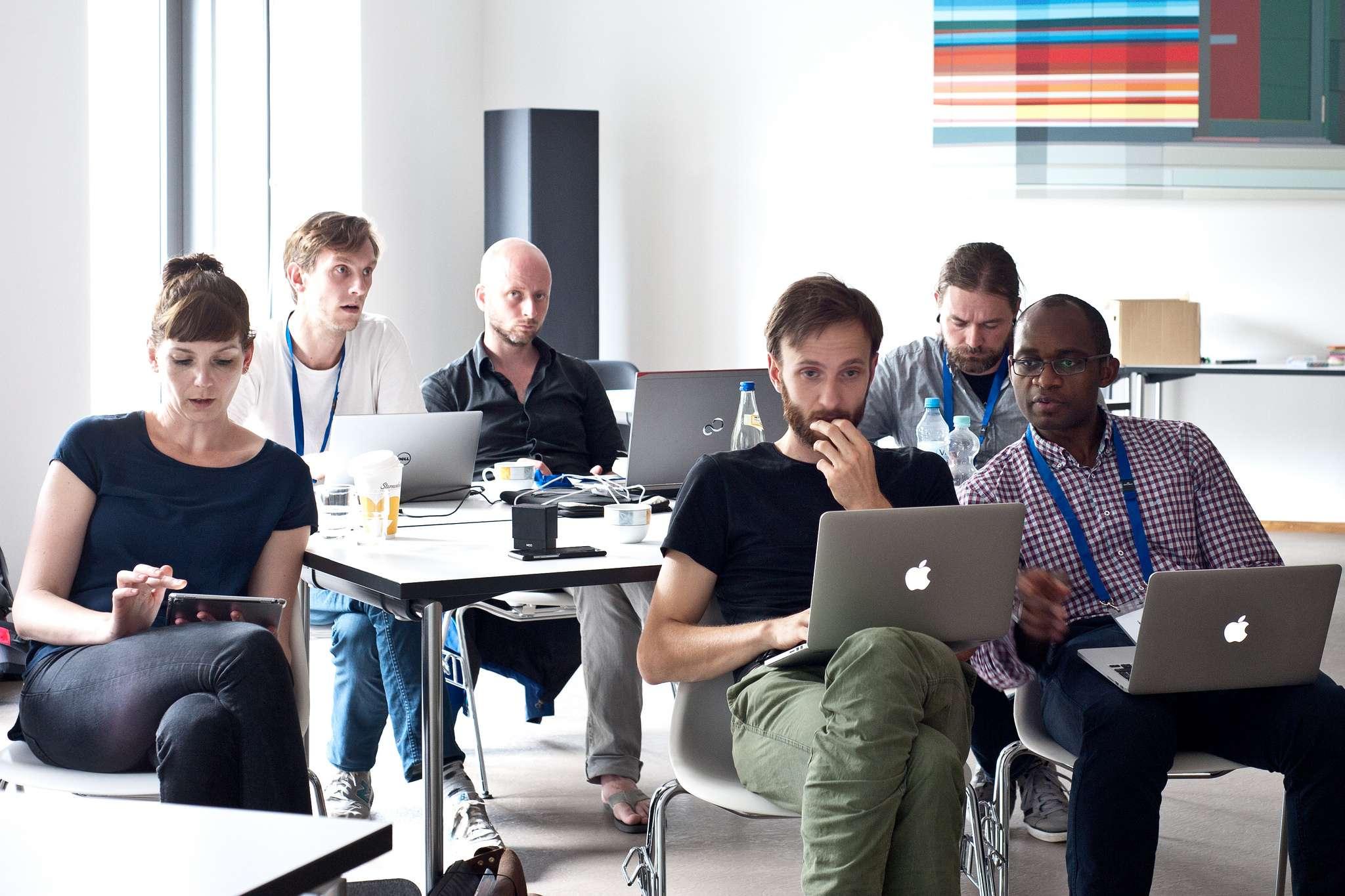 Foto des Konferenzraums mit mehreren Teilnehmenden, die gespannt in ihre Laptops blicken oder gemeinsam an OER-Problematiken arbeiten.