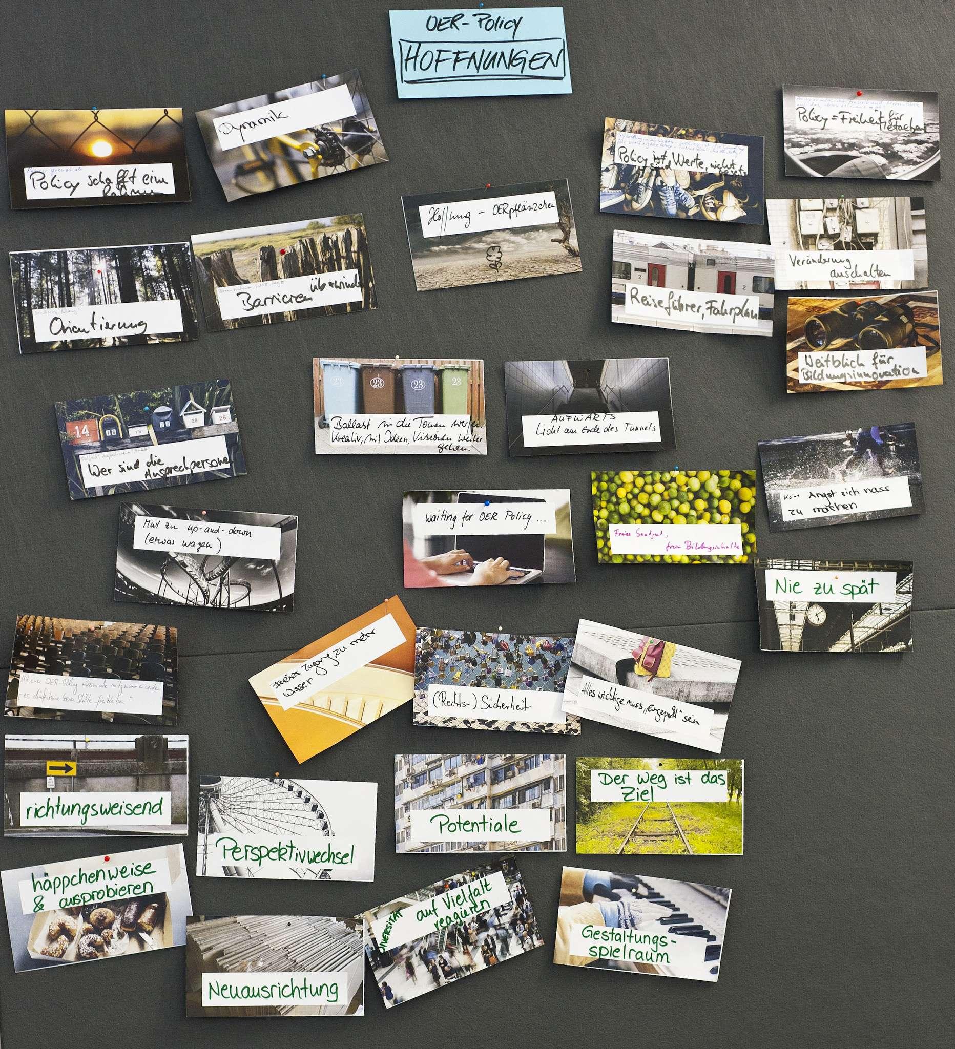 """Das Bild zeigt eine Metaplanwand mit sehr vielen Bildern, die assoziativ OER zugeordnet wurden. So zum Beispiel ein Zaun, der mit """"Policy schafft einen Rahmen"""" assoziiert wurde."""